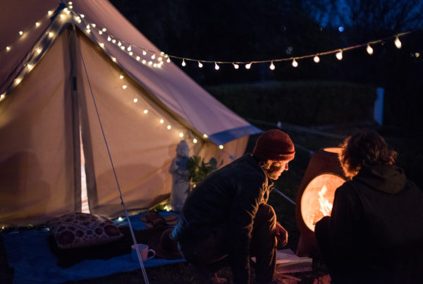 Two men check the fire in front of their canvas Stout Tent Stargazer bell tent